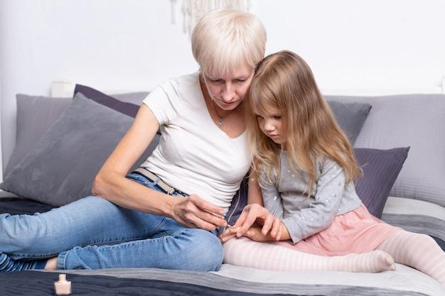 Grand-mère et petite-fille peignant leurs ongles avec du vernis assis sur le lit