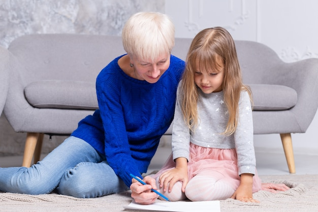 Grand-mère et petite-fille peignent ensemble au sol du salon. une femme adulte aide l'enfant à dessiner une image