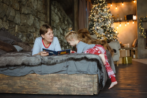 Grand-mère et petite-fille en pyjama de noël lisant un livre, allongées sur le lit du chalet. concept de famille de noël.