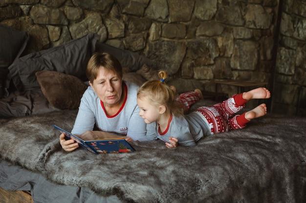 Grand-mère et petite-fille en pyjama de noël lisant un livre, allongées sur le lit du chalet.