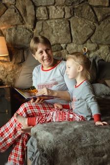 Grand-mère et petite-fille s'amusent ensemble en lisant un livre sur le lit