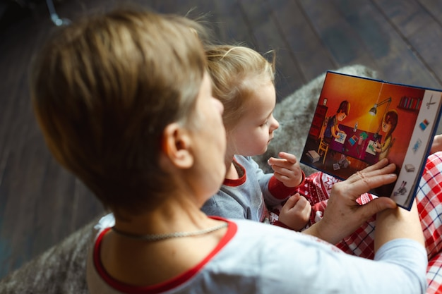 Grand-mère et petite-fille s'asseoir sur un lit en pyjama et lire un livre