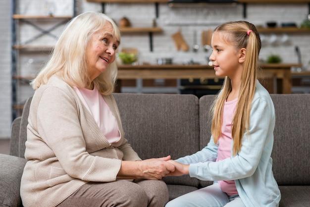 Grand-mère, petite-fille, tenant mains, vue frontale