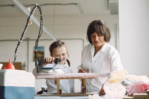 Grand-mère avec petite-fille de vêtements en fer dans l'usine