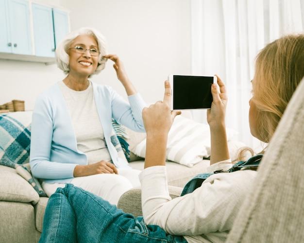 Grand-mère posant avec bonheur pour sa petite-fille faisant des photos