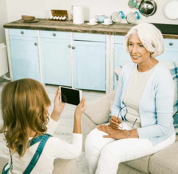 Grand-mère posant pour sa petite-fille nouvel appareil photo