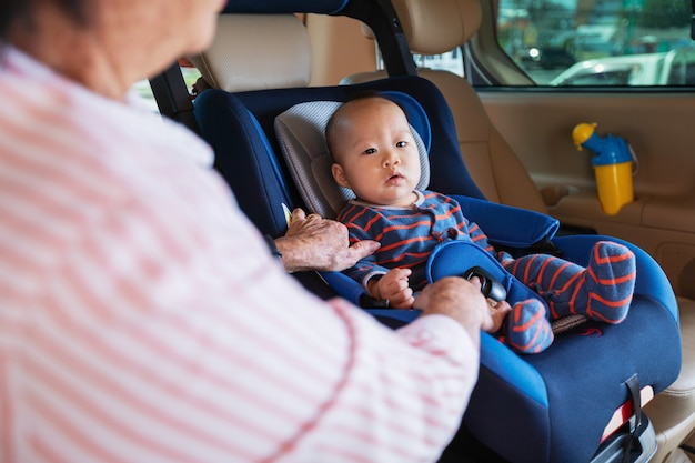 La grand-mère prend soin de sa petite-fille dans une voiture, l'aide et encourage