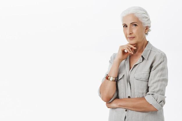 Grand-mère réfléchie à la satisfaction, fond blanc
