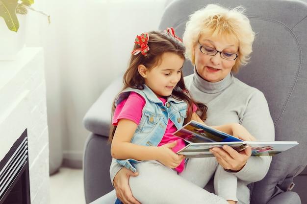Grand-mère regarde album photo avec son petit-enfant