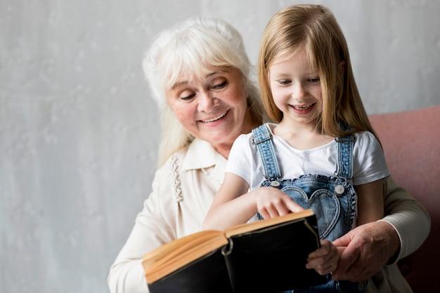 Grand-mère de smiley lisant pour petite fille