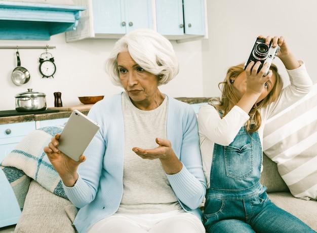Grand-mère et son petit-enfant ne peuvent pas comprendre les gadgets de l'autre