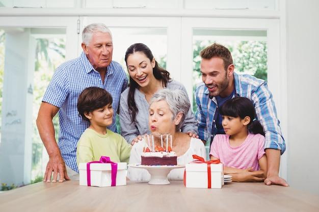 Grand-mère soufflant des bougies d'anniversaire avec la famille