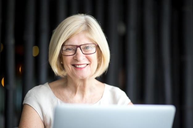 Grand-mère souriante dans les lunettes utilisant un ordinateur portable