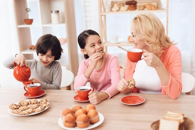 Grand-mère souriante avec des enfants buvant du thé le matin
