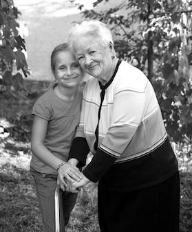 Grand-mère souriante avec petite-fille dans le parc