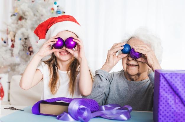 Grand-mère souriante avec petite-fille décorant des cadeaux à noël