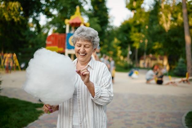Une grand-mère souriante tient de la barbe à papa dans un parc d'attractions d'été. mode de vie des personnes âgées. grand-mère drôle s'amusant à l'extérieur, vieille personne de sexe féminin sur la nature