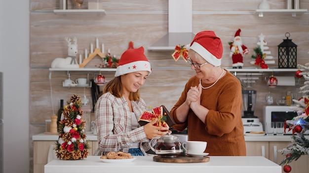 Grand-mère surprenante petite-fille avec emballage cadeau présent pendant les vacances d'hiver traditionnelles