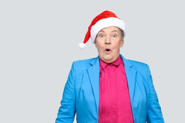 Grand-mère surprise dans un style décontracté coloré avec un costume bleu et un bonnet rouge de noël debout et regardant la caméra avec un visage étonné et une bouche et des yeux ouverts. intérieur, isolé sur fond gris
