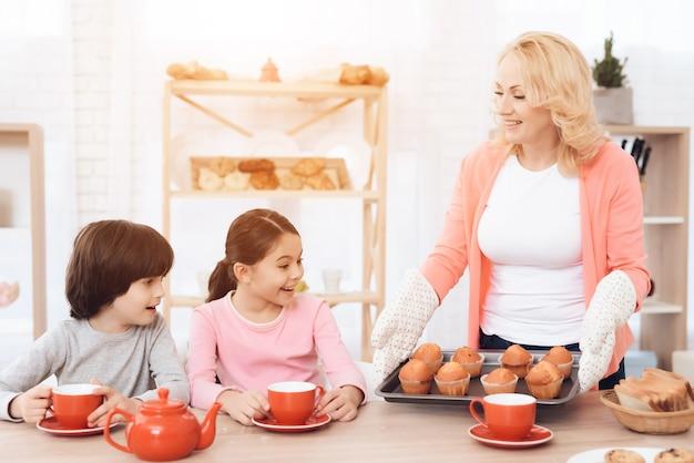 Grand-mère tenez le plateau avec le concept de petit déjeuner de muffins
