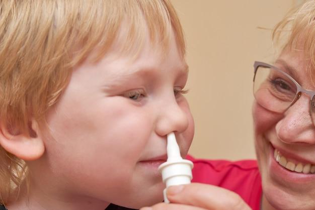 Grand-mère verse des gouttes nasales à un enfant qui traite des enfants à la maison