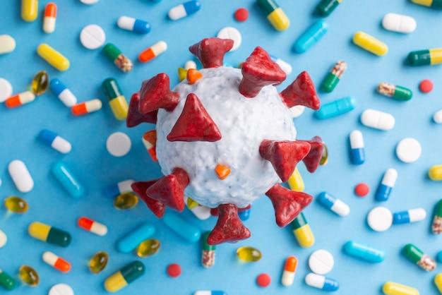 Grand modèle de cellule de coronavirus sur des pilules et des capsules sur tableau bleu