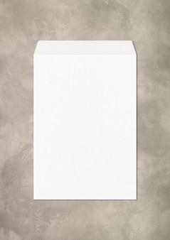 Grand modèle de maquette d'enveloppe blanche isolé sur béton