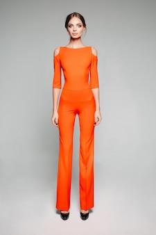 Grand modèle en salopette orange décontractée et talons hauts.