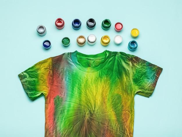 Un grand nombre de bidons de teintures textiles et un tee-shirt tie dye sur fond bleu. mise à plat.