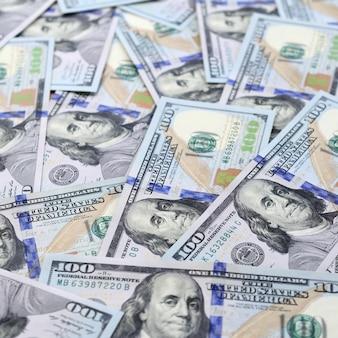 Un grand nombre de billets en dollars américains d'un nouveau modèle avec une bande bleue au milieu. vue de dessus