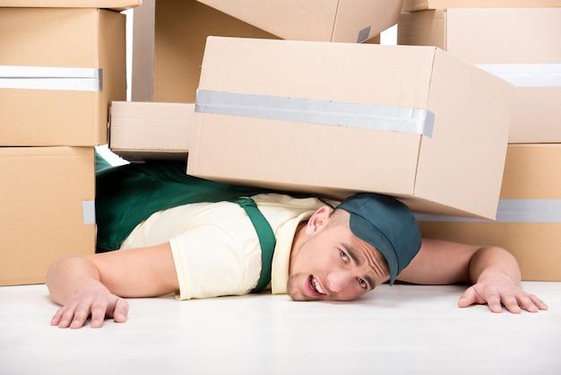 Un grand nombre de cartons sont tombés sur un jeune homme.
