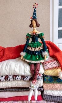 Un grand nombre de chandails et de pulls de différentes couleurs pliés en deux piles et un jouet de poupée fabriqué à la main.