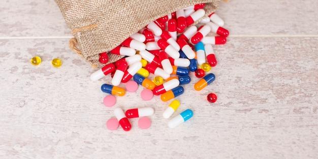 Un grand nombre de différentes pilules colorées sur un fond de table