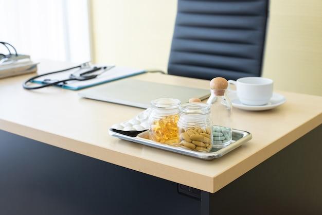 Un grand nombre de médicaments, pilules et autres médicaments différents sur la table en bois avec du matériel médical en arrière-plan.