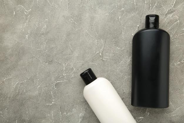 Un grand nombre de produits cosmétiques différents pour le soin des cheveux sur fond gris. vue de dessus