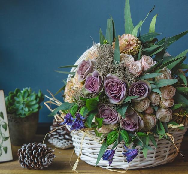 Grand panier de fleurs mélangées, debout sur une table avec des cônes de noël