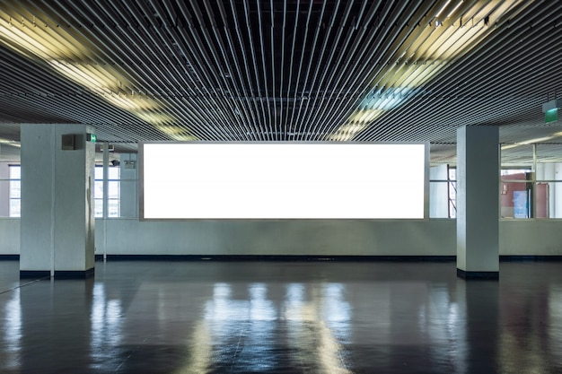 Grand panneau d'affichage dans un couloir métallique avec fenêtres transparentes