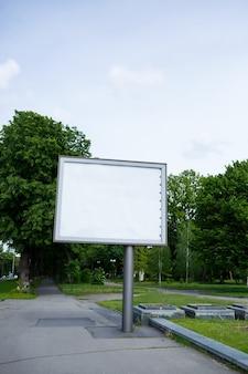 Un grand panneau d'affichage en métal dans la rue avec une place pour votre publicité, un panneau d'affichage sur fond d'arbres
