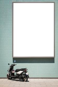 Grand panneau d'affichage vierge sur un mur vert, une moto noire moderne se tient à proximité