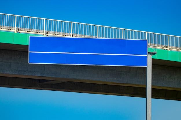 Grand panneau routier vierge avec ciel bleu dégradé.
