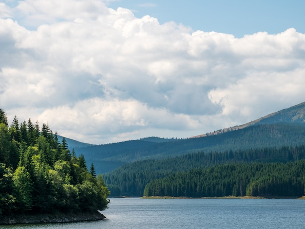 Grand paysage de roumanie avec montagnes, lac, arbres et nuagesdans une journée ensoleillée d'été