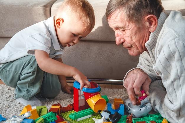 Grand-père âgé joue avec son petit-fils avec des blocs en plastique