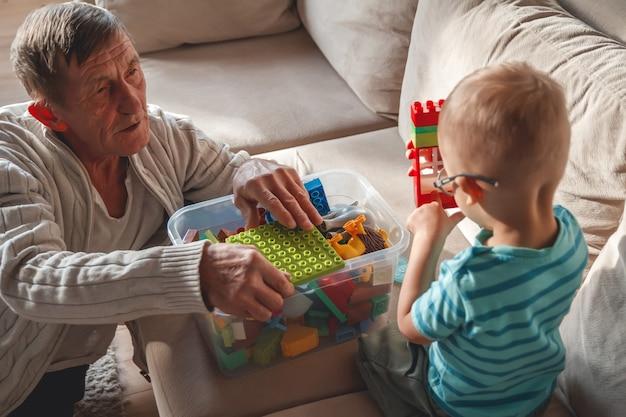 Le grand-père âgé joue avec son petit-fils avec des blocs en plastique
