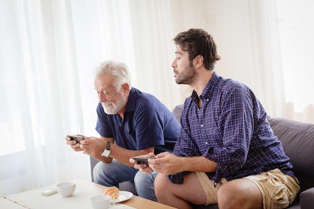 Grand-père aîné heureux de s'amuser avec son fils à la maison en jouant ensemble à un jeu mobile.