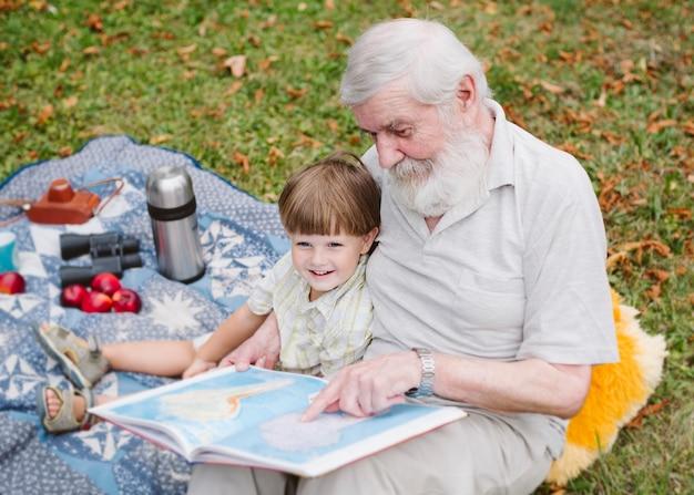 Grand-père à angle élevé lisant pour petit-fils