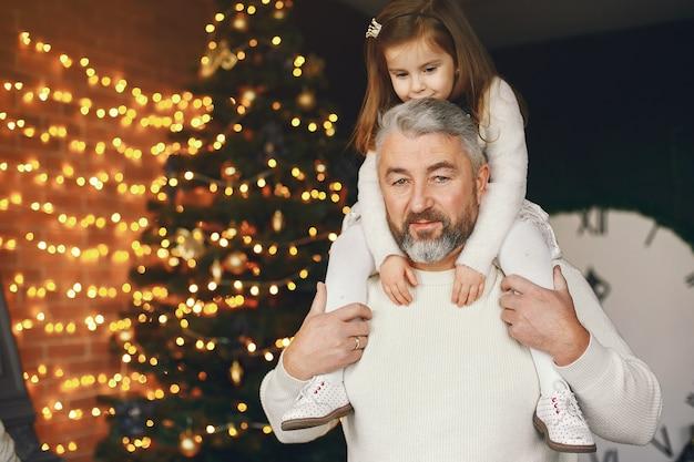 Grand-père assis avec sa petite-fille. célébrer noël dans une maison chaleureuse. homme dans un pull en tricot blanc.