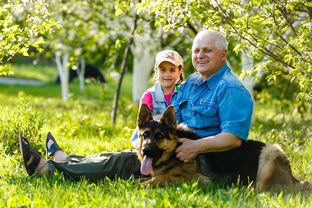 Grand-père avec chien petite-fille et un chien dans le jardin