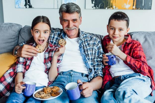 Grand-père avec deux jolis petits-enfants mangeant des biscuits et regardant un film