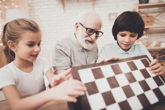 Un grand-père et des enfants ouvrent un échiquier à la maison