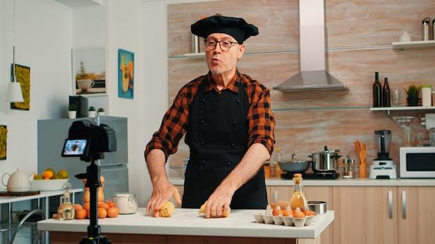Grand-père enregistrant une vidéo de nourriture dans la cuisine, préparant une pizza maison. chef influenceur blogueur à la retraite utilisant la technologie internet pour communiquer, bloguer sur les réseaux sociaux avec un équipement numérique
